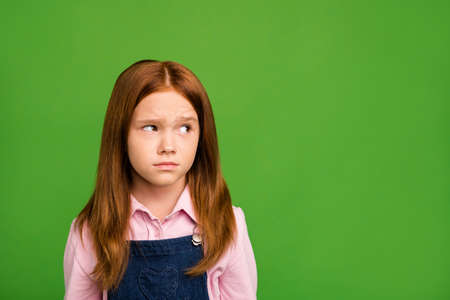 Closeup photo of little ginger schoolchild in front of blackboard thinking over answer teacher question have doubts wear denim overall pink shirt isolated green background