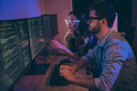 Photo de profil de celui-ci spécialiste deux hommes d'affaires s'asseoir sur des chaises de nuit coworking regarder des moniteurs corriger les erreurs bugs écriture interface code frontal bureau à l'intérieur Banque d'images