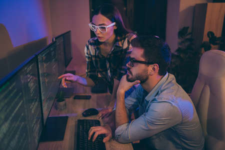 Profile photo of it specialist two serious guy lady business people night coworking watch direct monitors errors bugs writing interface back-end code office indoors Banque d'images