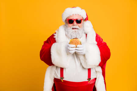 Portrait of funny funky fat santa claus dont care about health eat fast food big sandwich on x-mas tradition celebration wear style stylish suspenders isolated over shine color background