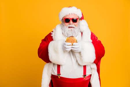 Retrato de divertido papá noel gordo funky no se preocupan por la salud comer sándwich grande de comida rápida en la tradición de Navidad celebración llevar estilo tirantes elegantes aislados sobre fondo de color brillante