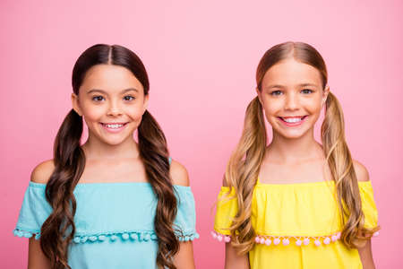 Photo of two beautiful little school ladies classmates summer holidays wear bright off-shoulders yellow blue blouse dresses isolated pink color background