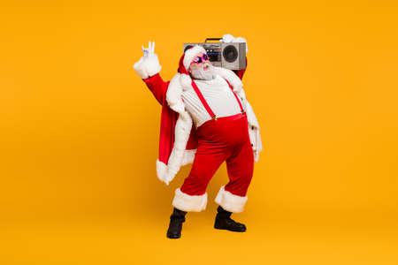 Full length photo of funny fat santa claus hipster with big belly hold boombox have fun listen christmas carols celebrate x-mas noel party wear red hat headwear boots isolated yellow color background