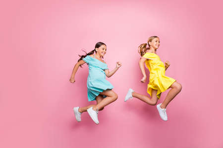 Full body profile photo of two friendship small ladies models jumping high hurry home summer holidays begin wear blue yellow dresses isolated pink color background Stockfoto - 133269368