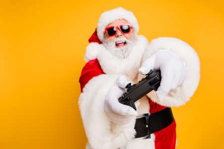 I will win. Portrait of funky funny crazy hipster santa claus play videogame use joystick having holly x-mas jolly newyear celebration isolated over yellow color background