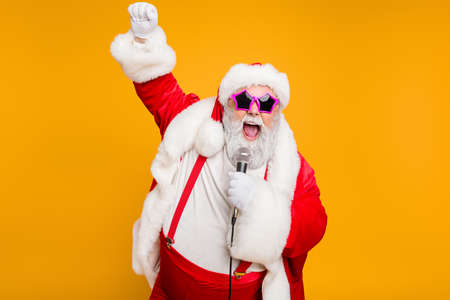 Grey haired stylish christmas grandfather in red hat cap celebrate x-mas party hold microphone sing noel carols feel funky with big belly wear suspenders isolated over yellow color background Imagens