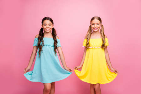 Photo of two people beautiful small school ladies classmates spend summer holidays together lovely sweet street look wear blue yellow dresses isolated pink color background