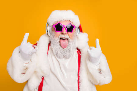 Close up photo of crazy funny hipster santa claus show horns sign tongue-out want rock-and-roll concert instead x-mas tradition celebration wear hat trendy suspenders isolated yellow color background