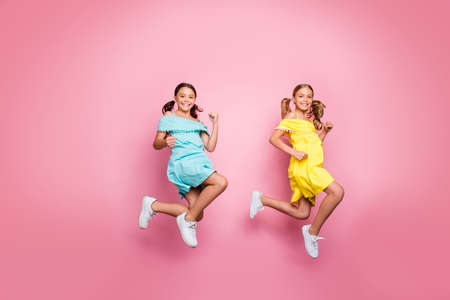 Full size profile photo of two friendship small sisters ladies models jumping high hurry home summer holidays wear blue yellow dresses isolated pink color background Stockfoto - 133269388
