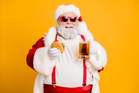 Portrait of funny funky santa claus with big belly want relax rest on x-mas celebration party hold glass of beer meat sandwich wear stylish suspenders red hat headwear isolated yellow color background Imagens