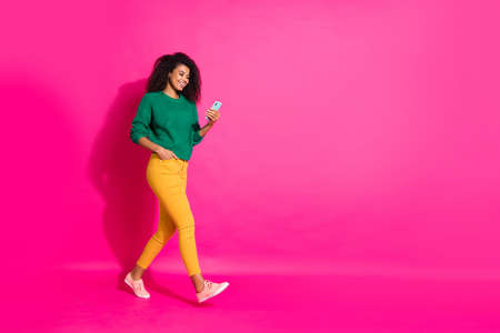 Full size profile side photo of wavy hair positive cheerful girl use mobile phone go walk on autumn fall holidays chill wear green pullover yellow pants sneakers isolated pink color background