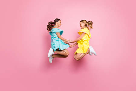 Full body profile photo of two small sisters girlfriends jumping high together last studying day holding hands wear blue yellow dresses isolated pink color background Stockfoto - 133269395