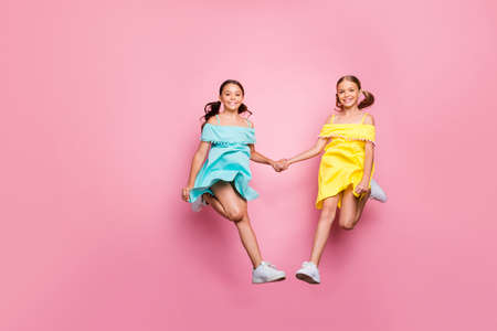 Full body photo of two small sisters girlfriends jumping high walking home together last studying day wear blue yellow dresses isolated pink color background