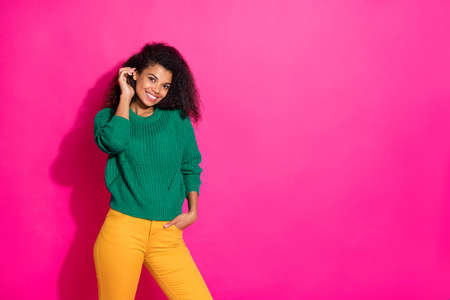 Portrait of cheerful positive afro american girl enjoy free time with her friends in autumn fall listen feel content wear green pullover trousers isolated over pink color background