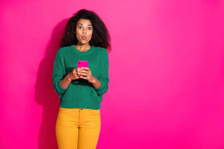 Portrait of impressed dark skin girl use her cellphone got social network, notification in blog wonder on winter holidays wear green pullover yellow pants isolated over pink color background