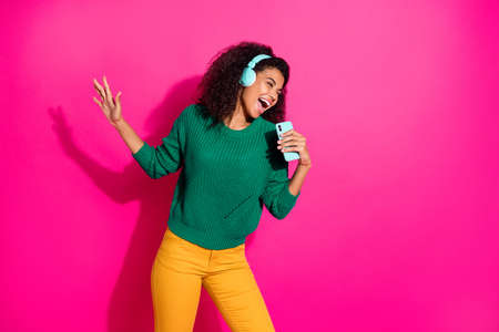 Portrait of crazy brown wavy hair student girl with headset use smartphone microphone sing songs hear playlist on winter holiday wear green pullover yellow pants isolated pink color background