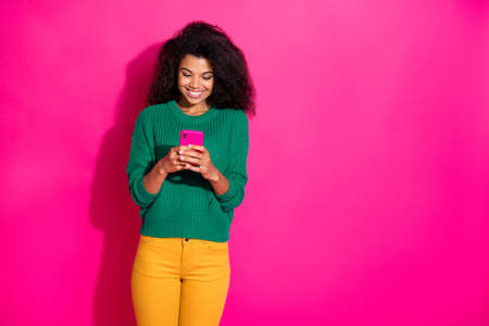 Portrait of positive cheerful afro american girl use smartphone type message communicate with blogger about blog on autumn fall weekends wear green jumper yellow pants isolated pink color background