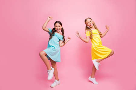 Full body profile photo of two people funny small school ladies models, rejoicing summer holidays start wear bright blue yellow dresses isolated pink color background