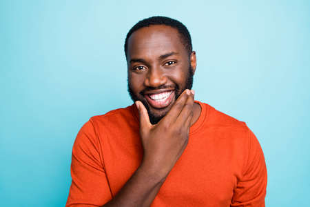 Closeup photo of attractive dark skin guy toothy beaming smiling touch cheekbones check beard growth temp wear orange pullover isolated blue color background