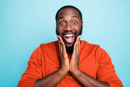 Closeup photo of attractive dark skin guy open mouth listen unexpected good news hands on cheekbones wear casual orange sweater isolated blue color background