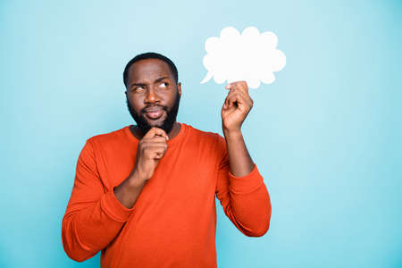 Photo of solving deciding man touching his beard in a fit of thoughts about his future concentrated on cloud he holds with hand isolated vivid color background blue