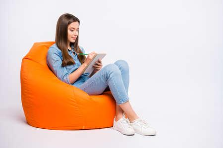 Profilseitenfoto in voller Größe von konzentriertem Mädchen, das ihre Hausaufgaben für die morgige Lektion in der Universität in ein Heft schreibt Standard-Bild