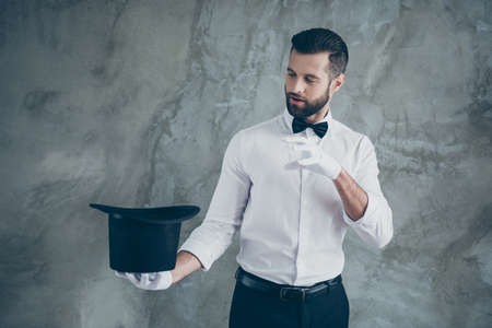 Photo of professional illusionist pretending to cast a spell to take something out of his cylindrical hat isolated over grey color wall concrete background