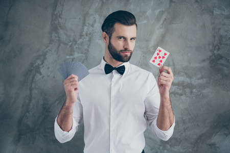 Foto de jugador de cartas inteligente que le muestra enfoques demostrando diferentes juegos de cartas aislados sobre fondo de color de pared de hormigón gris Foto de archivo