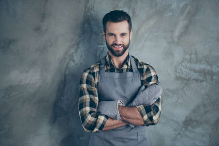 Photo of cheerful positive cook having fun rest after hard work day wearing gloves checkered shirt with toothy smile isolated grey wall concrete color background