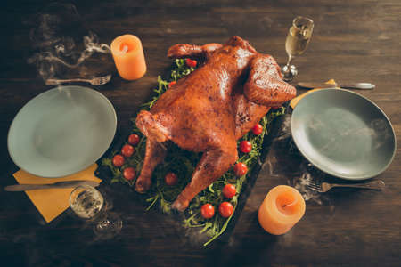 Top above high angle photo of delicious roast gourmet turkey on tray with herbs, red tomato served for thanksgiving tradition meal two people couple have plates forks knife glass isolated brown table