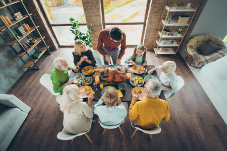 Top above high angle photo of big mature family celebrate october event thanksgiving day sit table enjoy meal corns vegetables harvest man slicing knife roasted meat dish in house Archivio Fotografico