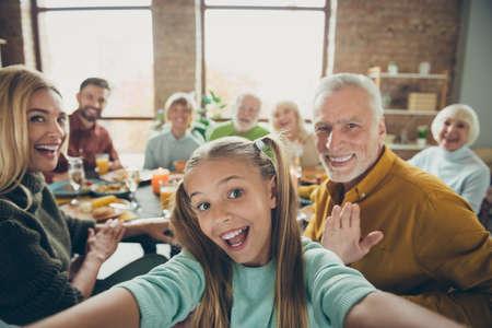 Video-oproep van gelukkige grote familie viert dankdag oktober herfst evenement feest klein klein meisje kind make selfie volwassen grootvader zeggen hallo golf hand grootmoeder geniet van maaltijd in huis