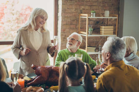 Big happy family meeting celebrate thanksgiving day sit table enjoy meal with roasted meat poultry retired woman say toast to small little kids pensioner relatives in house