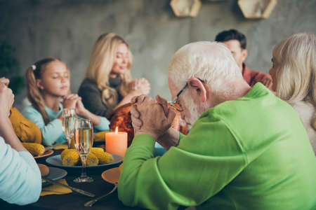Big family small little kids mature retired people meeting on thanksgiving day sit table with large banquet meal roasted meat wine candles pray in house
