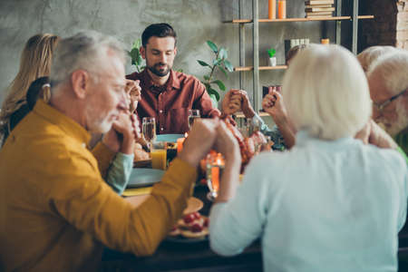 Big family of mature father mother small boy little girls pensioner celebrate fall october feasting holiday thanksgiving day pray sit table with chicken wine candles decoration in house