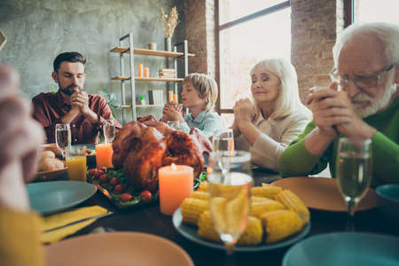 Big family father small little boy retired people gather relatives on event october celebration thanksgiving pray sit table with dinner corns harvest chicken meet in house Stock fotó
