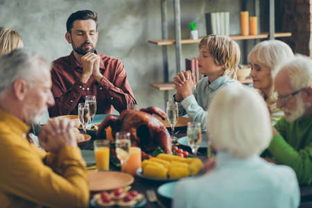 Big family celebrate thanksgiving day sit table have large feast meal food roasted meat corns alcohol pray in house indoors Stock fotó