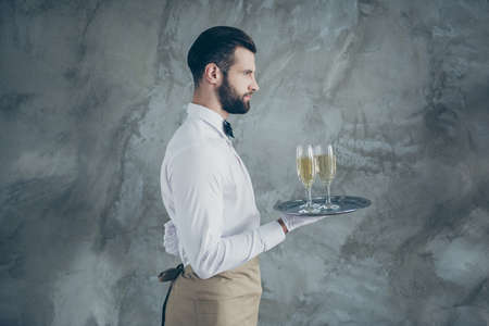 Side profile photo of attractive server holding tray with champagne glasses with bristle isolated grey concrete wall color background