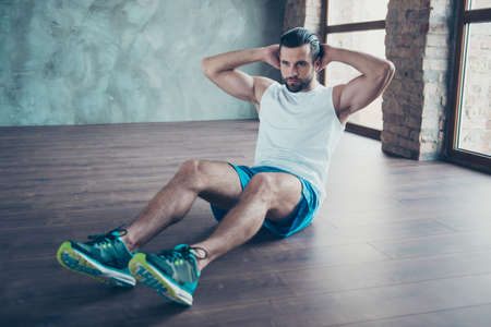 Photo of macho sportsman guy doing static sit ups sitting floor determined person sportswear tank-top shorts sneakers training house studio windows indoors Stock Photo