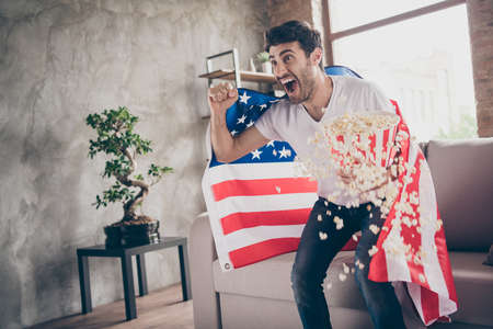 Photo of multiethnic crazy arab guy sitting sofa hold popcorn bucket raising fists supporting usa football team match american flag on shoulders coat flat room indoors