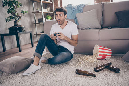 Photo of mixed race arabian guy sitting carpet leaning sofa hold joystick playing video game excited want win empty beer bottles popcorn on floor messy disorder flat indoors