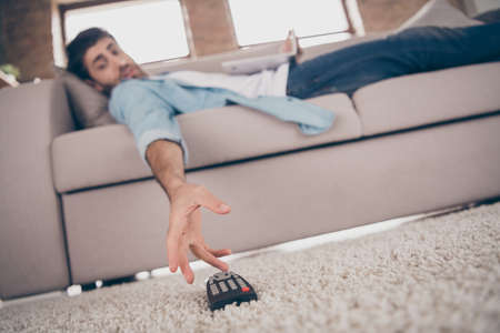 Low angle view photo of lazy mixed race arab guy lying comfy sofa cant take tv remote control gadget need change channel weekend apartments indoors Stockfoto
