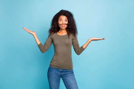 Portrait of funny funky afro american girl promoter have fake mustache hold hand recommend choice decision advice advertise wear trendy green outfit denim jeans isolated blue color background Stock Photo