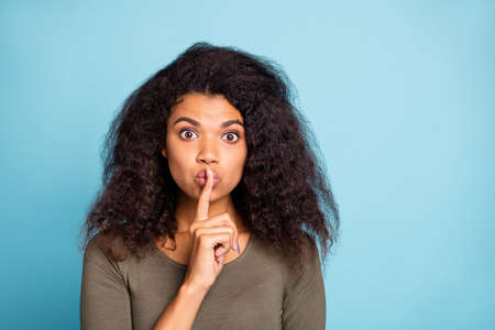 Keep secret. Close up photo of serious afro american girl hold her index finger near lips show mute sign tell dont share private novelty wear stylish green pullover isolated blue color background