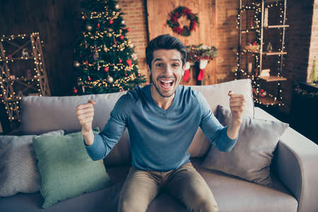 Portrait of funky guy relax sit cozy couch watch final world soccer cup match support team on newyear christmas eve scream yeah in house with x-mas fairy decoration toys illumination Stock Photo