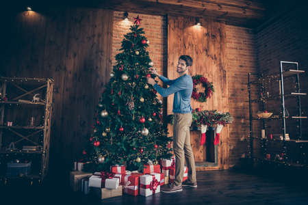 Full length body size turned photo of cheerful funky positive man hanging toys onto tree in pants trousers shoes smiling toothily looking at camera Reklamní fotografie