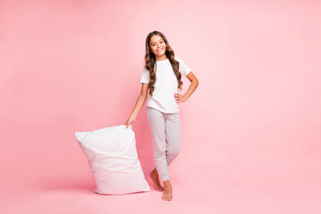 Full length body size view of her she nice attractive cute sweet lovely cheerful wavy-haired pre-teen girl carrying holding in hands white soft pillow isolated on pink pastel color background