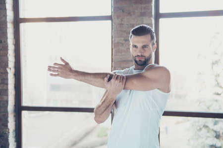 Photo of handsome beard guy preparing to morning training stretch warming up hand muscles sportswear tank-top shorts sneakers training house studio big windows indoors Stok Fotoğraf