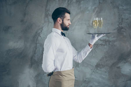 Profile side photo of attractive handsome in apron holding plate with glasses of champagne with bristle isolated grey color concrete wall background