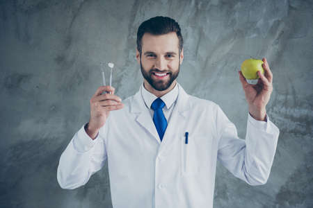 Photo of cheerful positive doctor holding instruments and apple wearing white coat smiling toothily isolated grey color concrete wall background